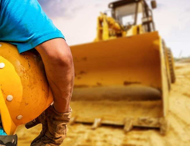 Construction worker with hard hat and bulldozer in front of him